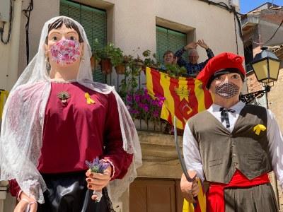 Els gegants saludant a un dels balcons del poble