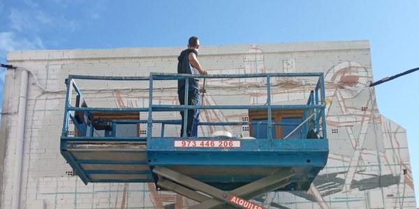 Slim Safont pintant la façana de l'oficina de turisme.